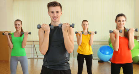 Young beautiful peoples engaged with dumbbells in gym photo