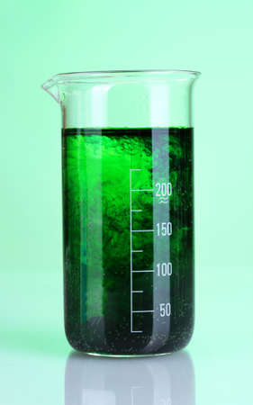 brightly ink in a flask with water on green  Stock Photo