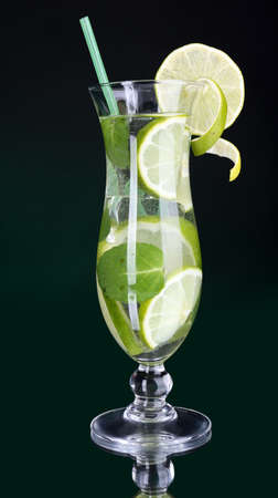 Glass of cocktail with lime and mint on table on dark green background photo