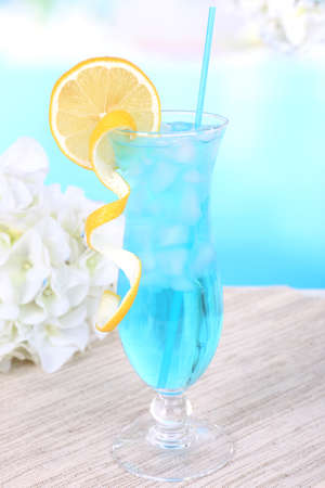 Glass of cocktail on table on light blue background photo