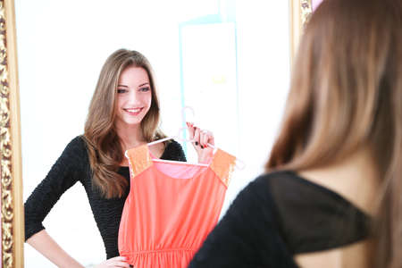Young beautiful woman trying dress front of mirror in room photo