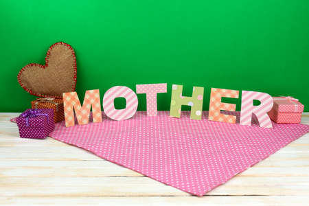 Mother- lettering of handmade paper letters on green background photo