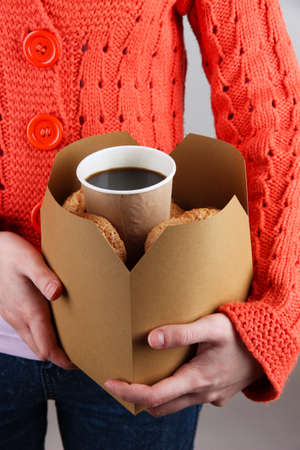coffee breaks: Woman holds box with coffee and cookies on grey background