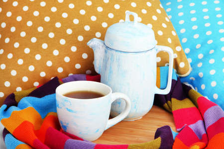 Cup and teapot with scarf on wooden stand on bed close up photo