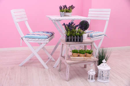 Garden chairs and table with flowers on wooden stand on pink background photo
