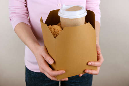 tea breaks: Woman holds box with coffee and cookies on grey background
