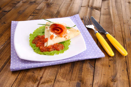 Pancake with salmon, red caviar and mayo, green onion, on plate, on color napkin, on wooden background photo