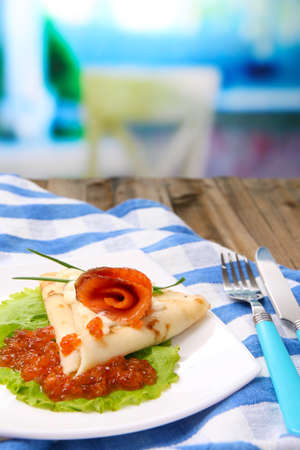 Pancake with red caviar, salmon and mayo, green onion, on plate, on color napkin, on wooden  table, on bright background photo