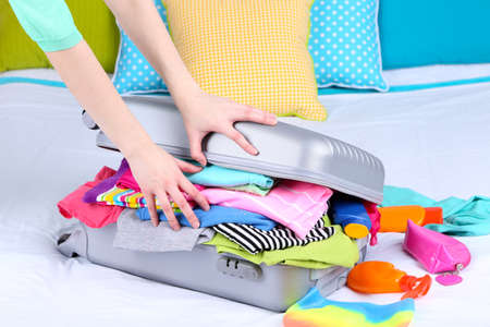 Girl collects suitcase on bed close-up photo
