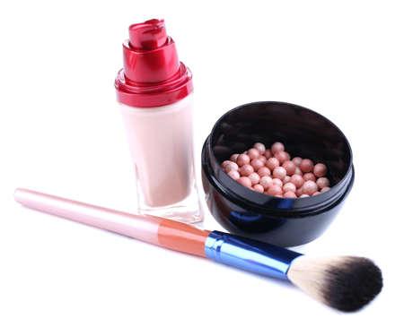 concealer: Composizione con correttore, palle di polvere e pennello isolato su bianco