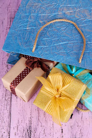 Presents with paper bag on wooden background photo