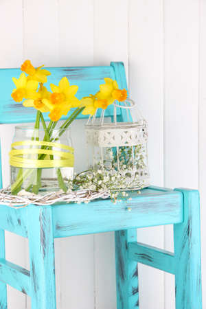 Beautiful spring flowers on blue old wooden chair  photo