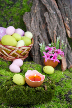 Conceptual Easter composition. Burning candle in egg, Easter eggs and flowers on green grass background, close-up photo