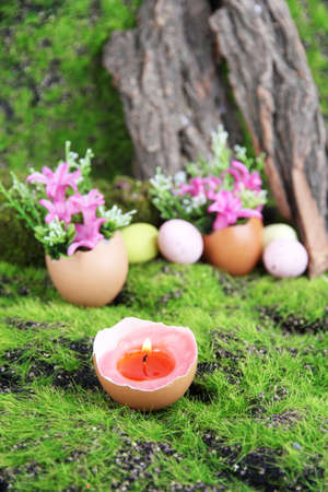 Conceptual Easter composition. Burning candle in egg and flowers on green grass background, close-up photo