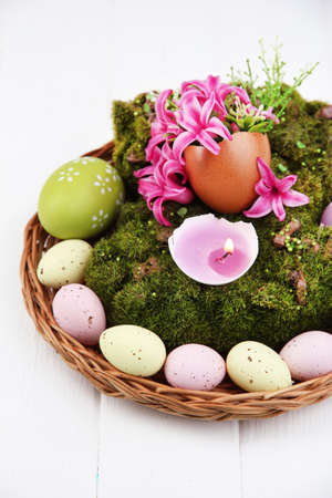 Conceptual Easter composition. Burning candle in egg, Easter eggs,  and flowers on decorative moss and wicker mat, on wooden background, close-up photo