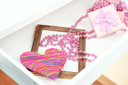 Gift box and beads in open desk drawer close up  photo