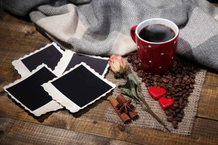 Composition with coffee cup, decorative hearts, plaid spices and old blank photos, on wooden background photo