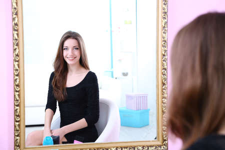 mirror reflection: Young beautiful woman sitting front of mirror in room
