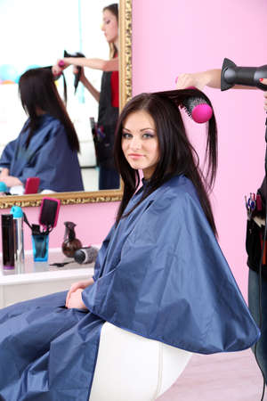 Beautiful woman hairdresser do hairstyle girl in beauty salon photo