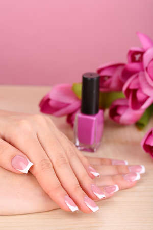 Beautiful woman hands with french manicure and flowers on table on pink background photo