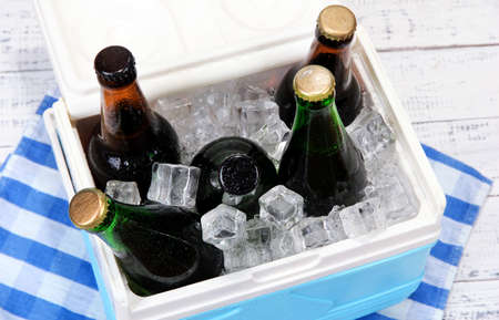Ice chest full of drinks in bottles on color napkin, on wooden background photo