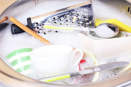 Utensils soaking in kitchen sink photo