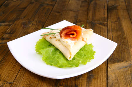 Pancake with salmon, and mayo, green onion, on plate, on wooden background photo