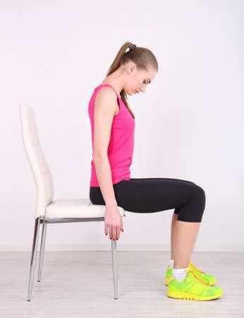Mladá krásná dívka fitness cvičení s židlí v tělocvičně Reklamní fotografie