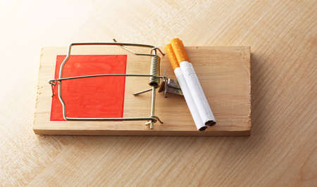 narcotism: Mousetrap with cigarette, on wooden background Stock Photo