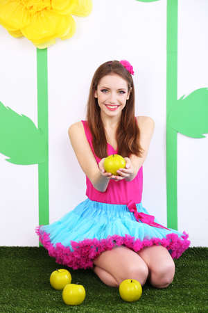 Beautiful young woman in petty skirt with apples on decorative background photo