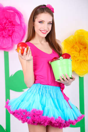 Beautiful young woman in petty skirt holding bucket of apples on decorative background photo