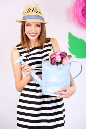 Beautiful young woman holding watering can on decorative background photo