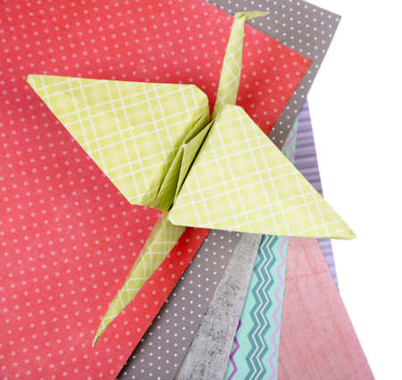 Origami crane and color papers isolated on white photo