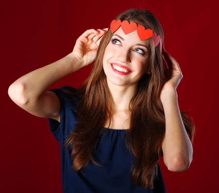 Attractive woman with with paper garland, on color background photo