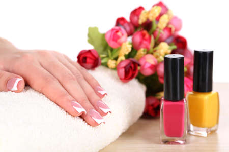Beautiful woman hands with french manicure and flowers on table on white background photo