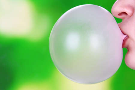 Person doing bubble with chewing gum on bright background photo