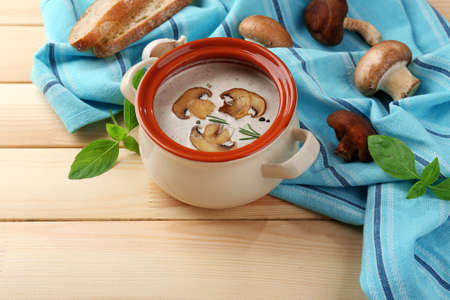 Mushroom soup in pot, on napkin,  on wooden background photo