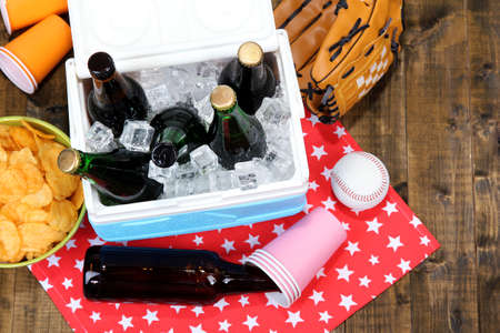 ice chest: Ice chest full of drinks in bottles on color napkin, on wooden background