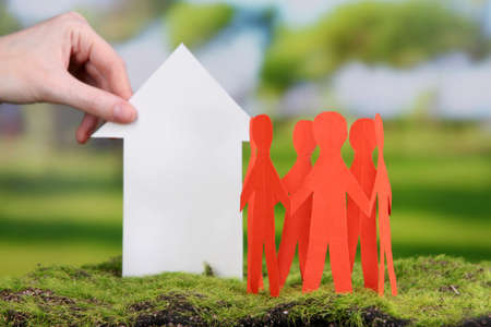 Little paper house in hand close-up, on green grass, on bright background photo