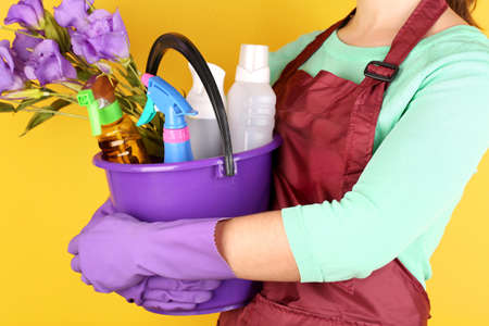 Housewife holding bucket with cleaning equipment on color background. Conceptual photo of spring cleaning.  Stock Photo - 27010585