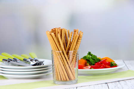 Bread sticks  in wicker basket on wooden table on light background photo