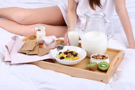 Woman in bed with light breakfast  Stock Photo