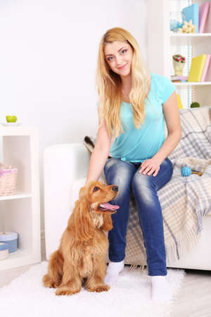 Beautiful young woman with cocker spaniel in room photo