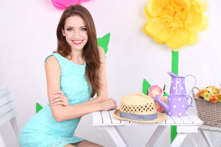 Beautiful young woman sitting on chair at table on decorative background photo