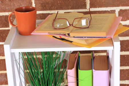 Composition with glasses and books, on cabinet, on color wall background photo