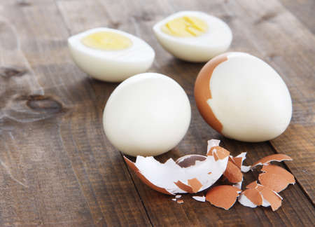 Peeled boiled egg on wooden background photo