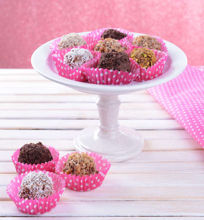 Set of chocolate candies on table on pink  photo