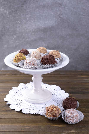 Set of chocolate candies on table on grey  photo