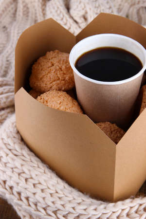 Hot coffee and cookies in box on knitted scarf  close-up photo