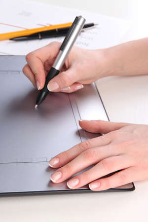stylus: Female hand using graphics tablet on table close up